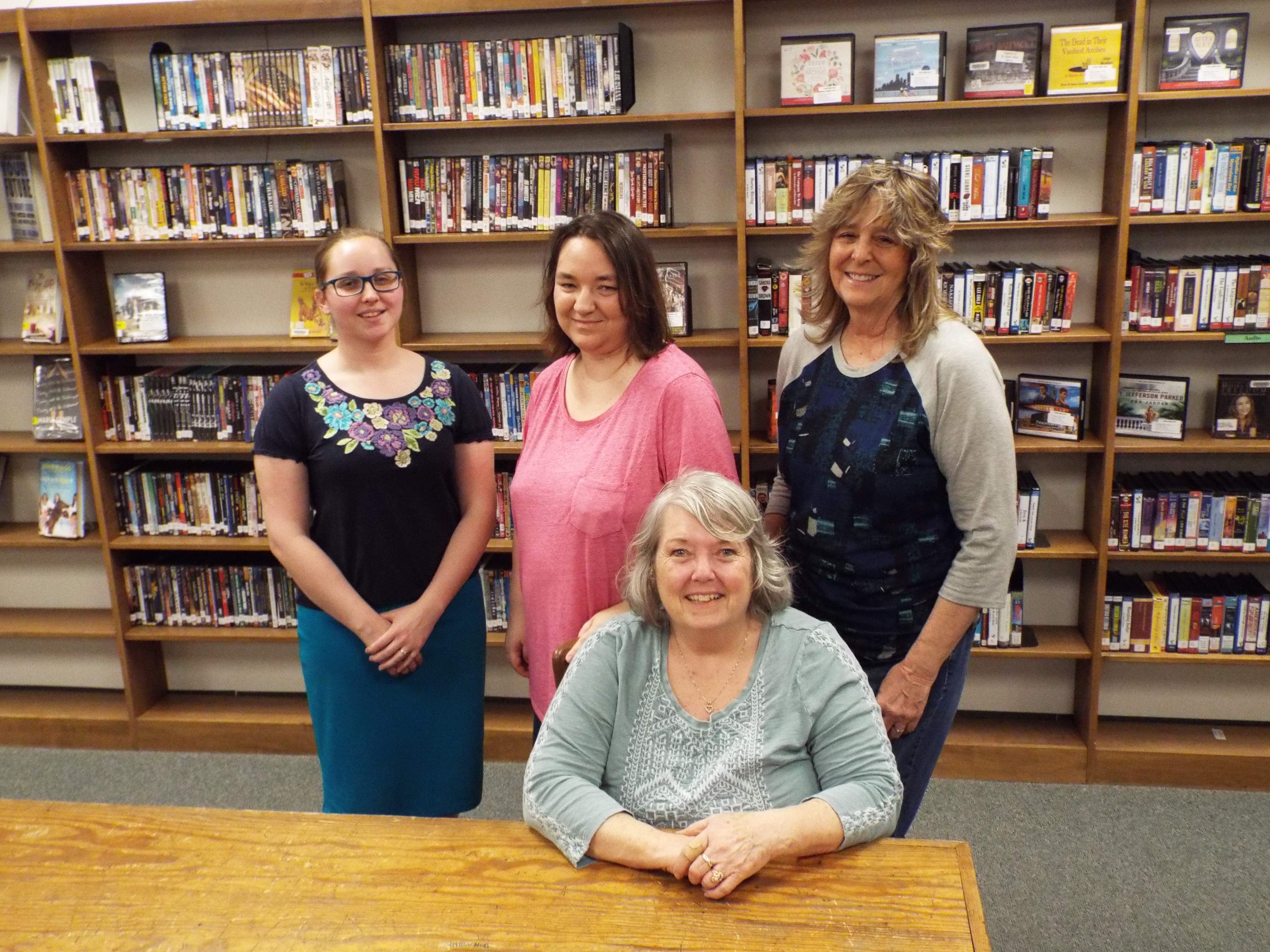 Several of the photographers whose work now hangs in the Du Quoin Public Library Gallery gather Monday evening for an artists' reception at the library. Standing from left are Brittany Elswick, Becky Hagerling and Jean Bullock. Pat Purnell is seated.