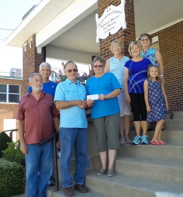 Denise Stearns, president of the Marion Garden Club, presents Sam Lattuca, president of Williamson County Historical Society, with a donation.