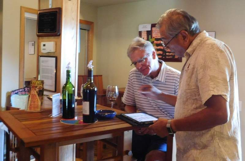 Doug Cross (left) of Goreville discusses his wine choices with David Ponce, owner of Monte Alegre Vineyard and Cellars. Cross is a regular customer. 'I realized my supply was low so I drove up to replenish,' he says. Cross enjoyed a tasting of new wines while Ponce filled his order.