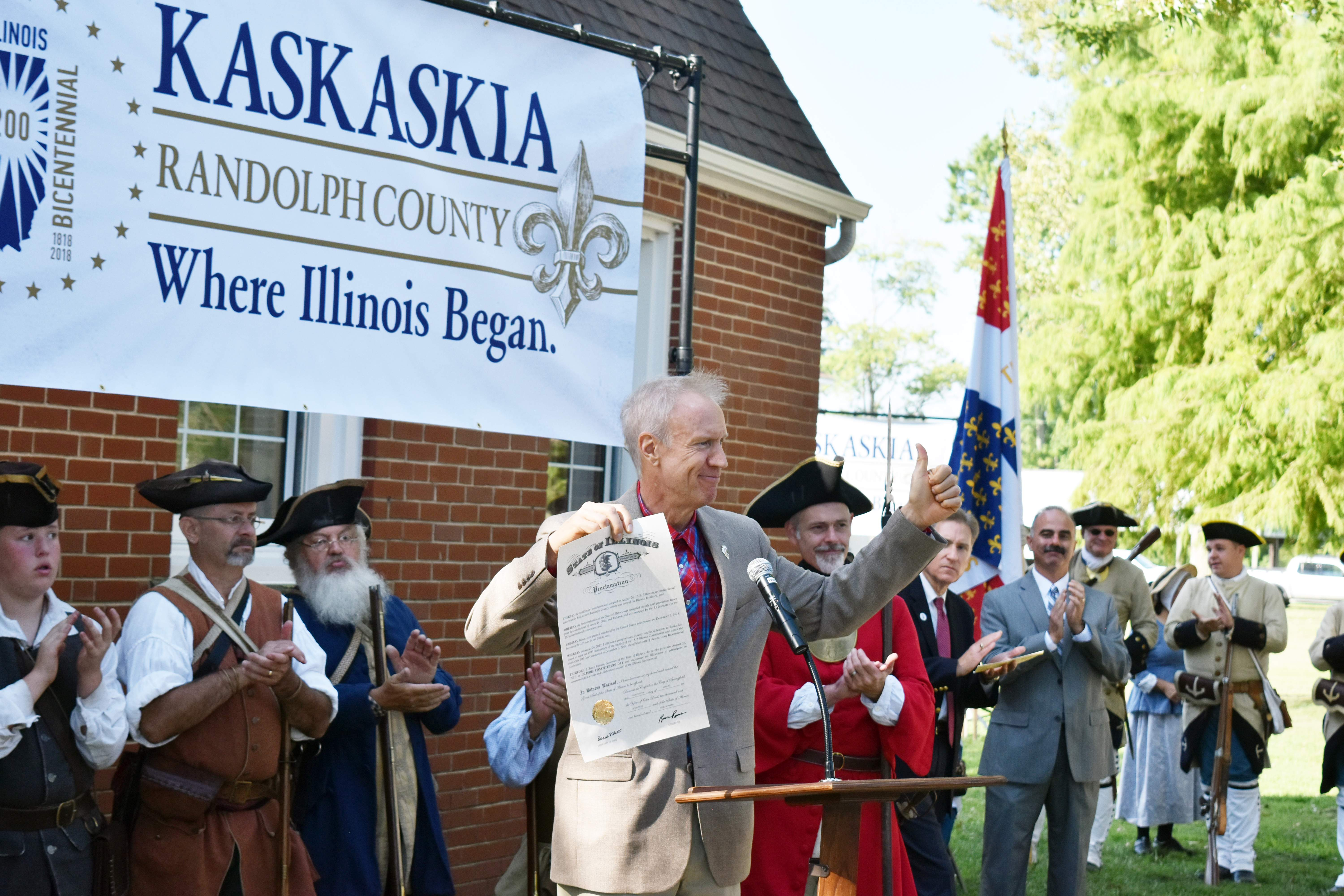 """Gov. Bruce Rauner gives a thumbs-up to the crowd after proclaiming Saturday as """"Constitution Day"""" in Illinois. Rauner, as well as Lt. Gov. Evelyn Sanguinetti and other state, county and local officials, were on Kaskaskia Island for the kickoff to the state's 100-day countdown to the Illinois bicentennial."""