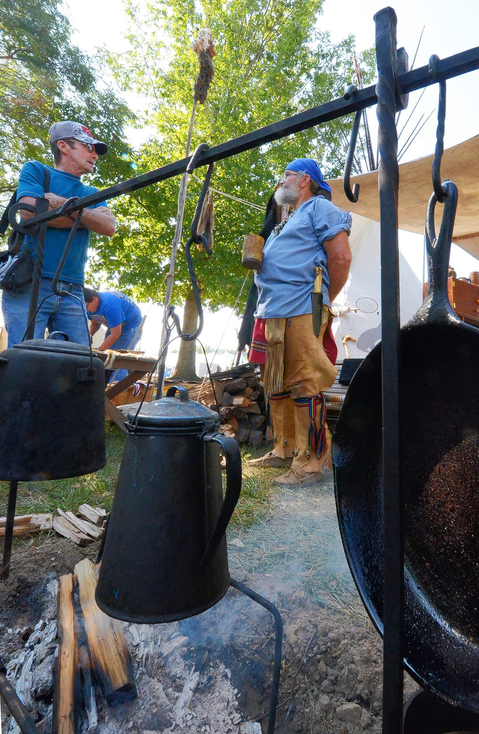 "Dennis Wood of Odin, on the left, visiting with re-enactor Bill Fox near a campfire Saturday said, ""I try to come down from Marion County every year for this. I still hunt a lot and fish a little, so this is right up my alley!"