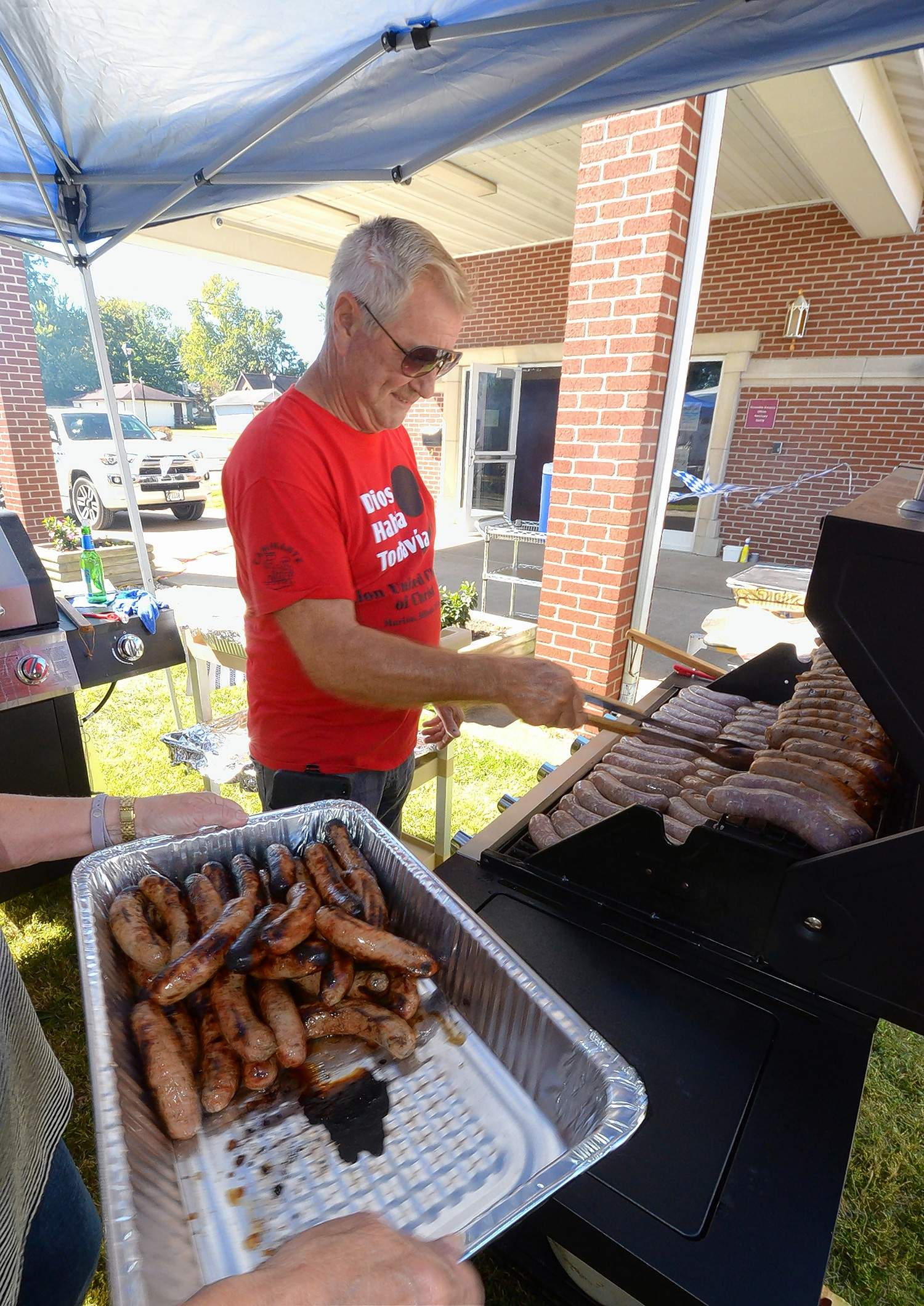 Church member Gene Ruehmkorff was busy at the grill Saturday cooking applewurst sausages for the hundreds of hungry guests in attendance at Zion United Church of Christ's second annual Oktoberfest.
