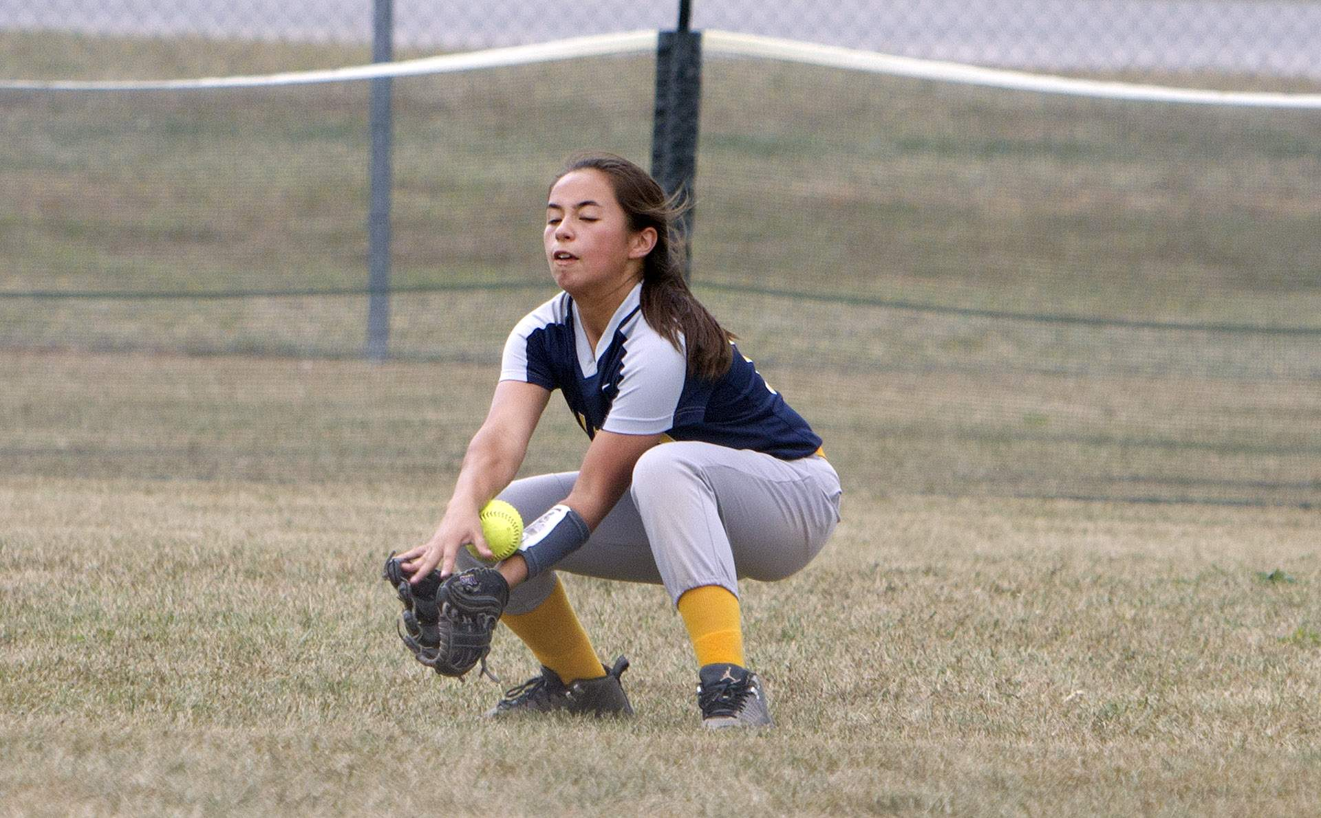 Ava Wong fields a ball in left field.