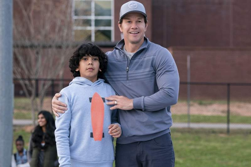 Juan (Gustavo Quiroz) and Pete (Mark Wahlberg) try to bond in 'Instant Family.'