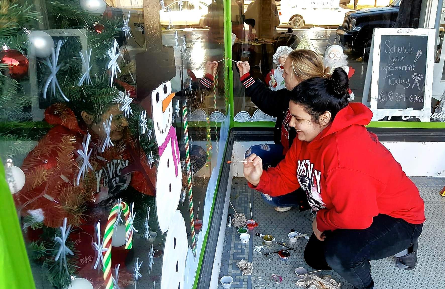 Nevaeh Casanova, front, and Kendall Overtuf work on creating a traditional Christmas scene on the windows at Steal the Show. Both girls are freshman art students at Johnston City High School.