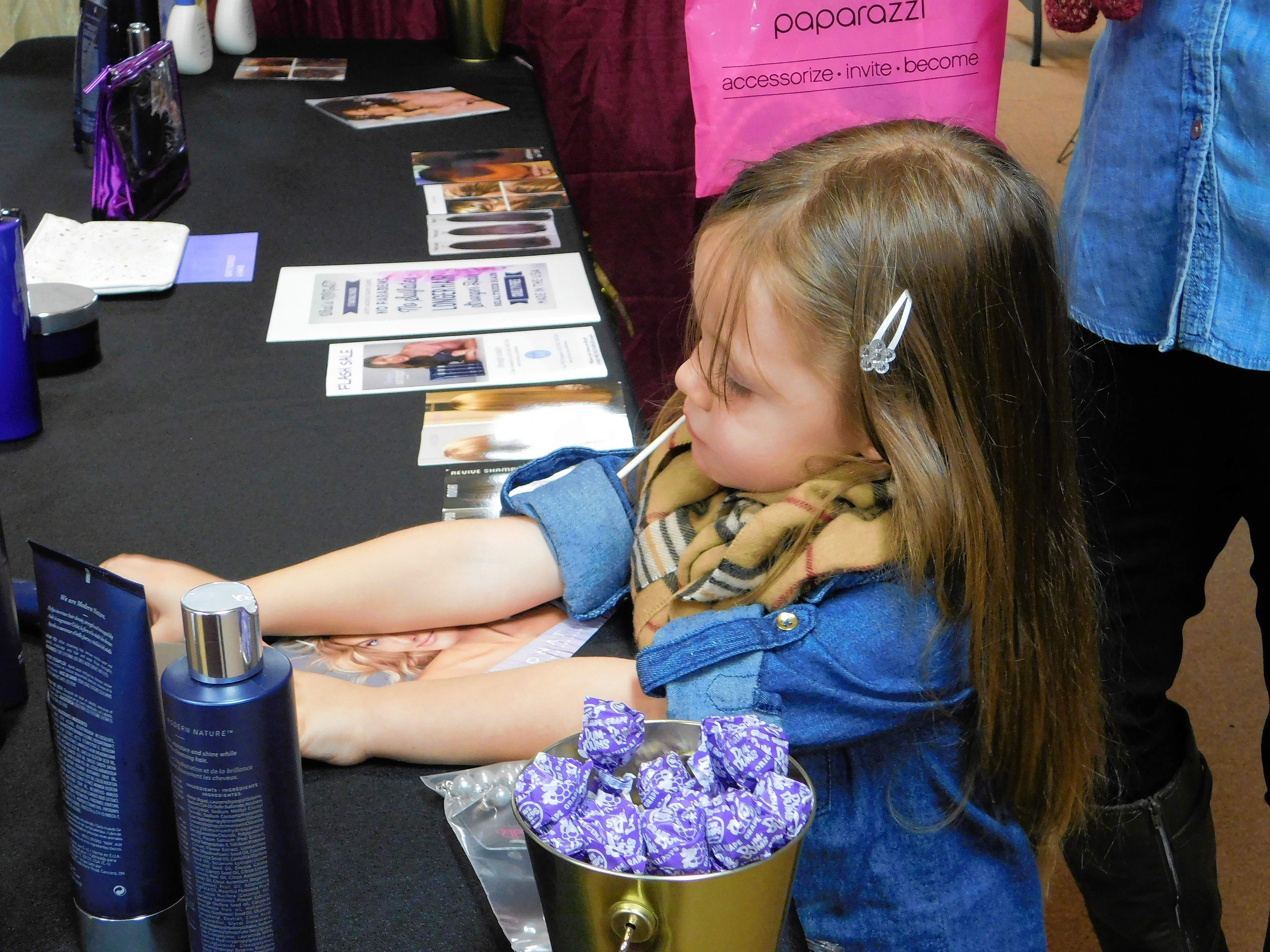 Khloe Watkins, 3, of Marion, is interested in Monat beauty products at  Callie James' booth at the Holiday Extravaganza held at the Marion Pavilion on Saturday.  The event drew in 40 vendors and roughly 400 visitors.