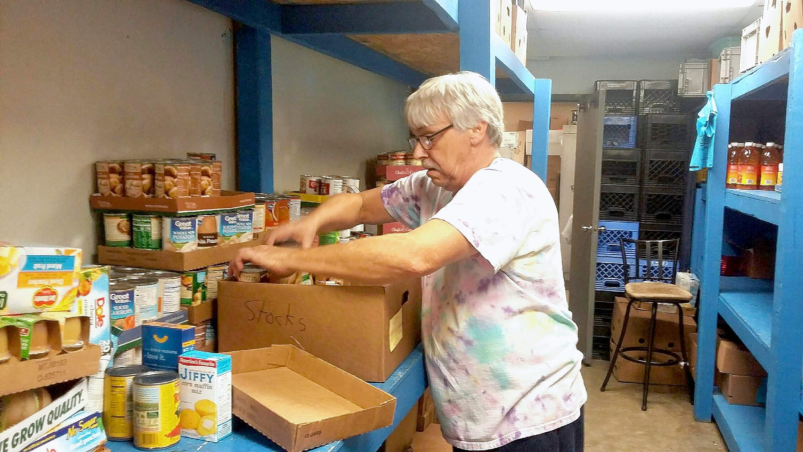"""Food pantry volunteer, """"Frenchie,"""" fills a Christmas Box Wednesday at the center."""