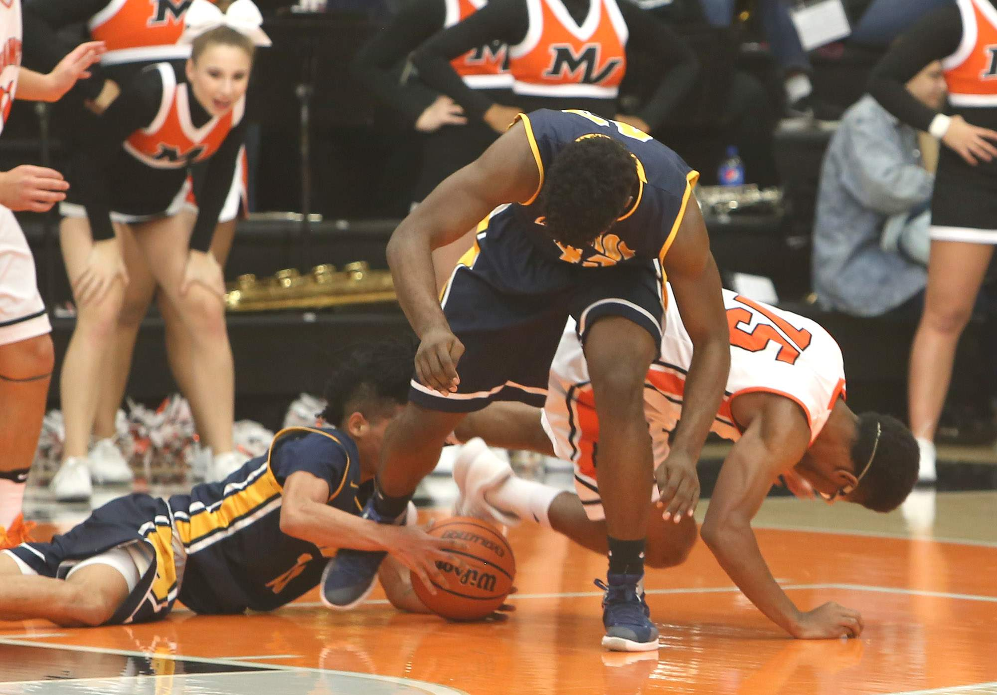 Korey Houston gathers a loose ball underneath Terrell Henderson.
