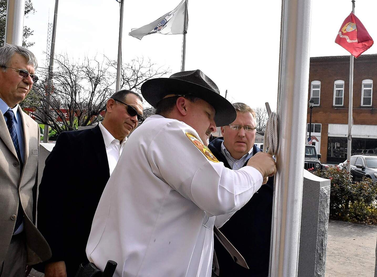 Perry County Sheriff Steve Bareis ties the bicentennial flag as Perry County Commissioners James Epplin, Robert Kelly and Dallas Bigham look on.