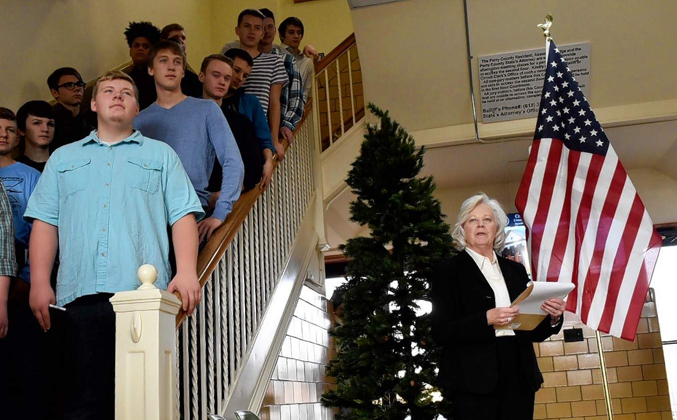 Mary Roe, who organized Monday's event, speaks Monday as members of the Pinckneyville Community High School choir look on.