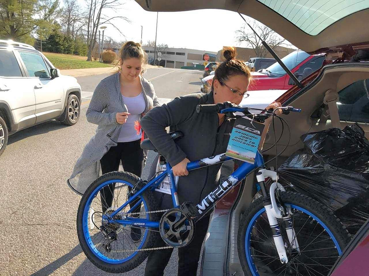 Niki Grajewski, clinical program manager at Centerstone, pushes a new bike into her vehicle to give to a needy child. With her is Jayden Stanley, a volunteer with the Poshard Foundation.