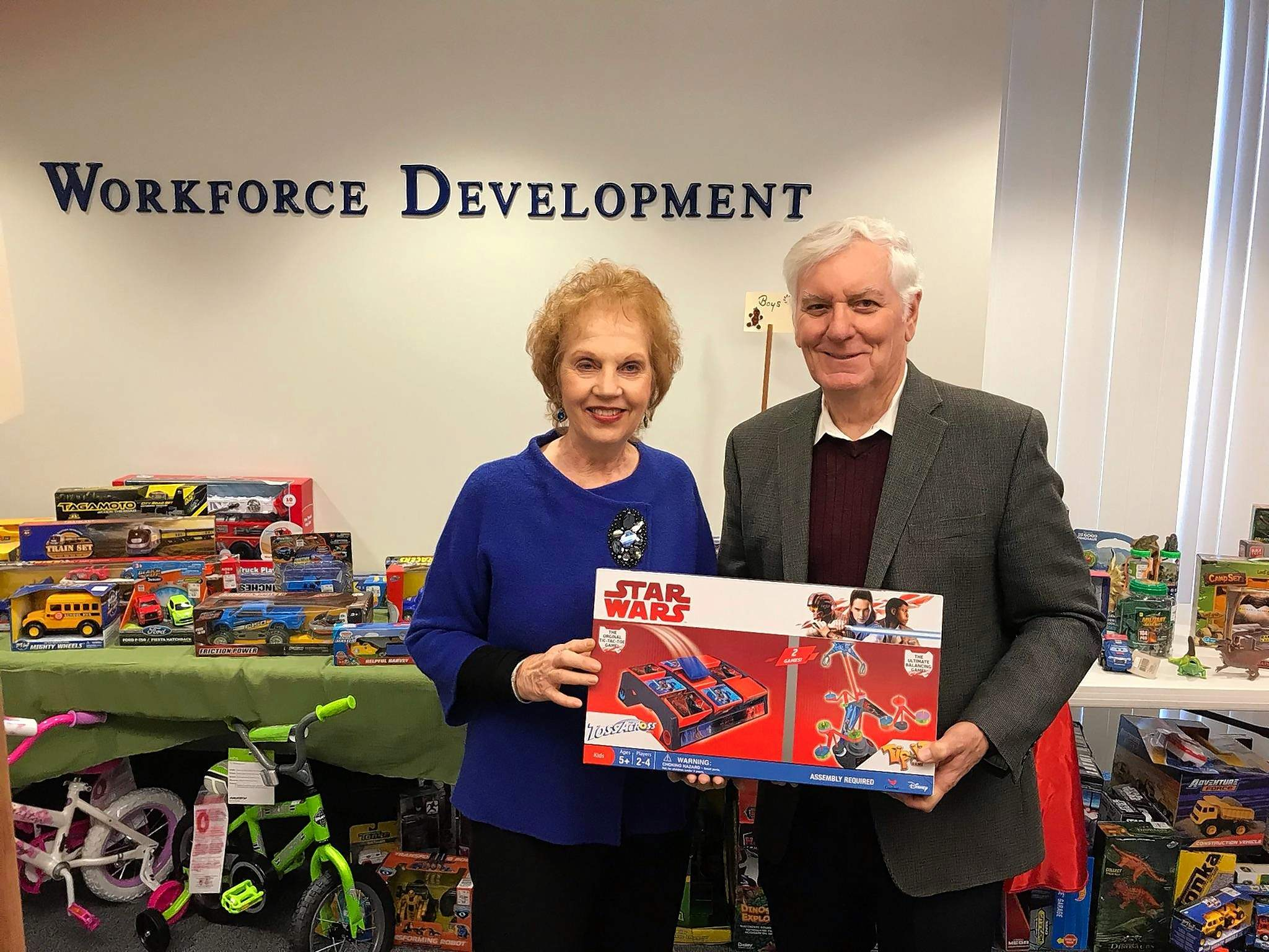 Poshard Foundation co-founders Jo and Glenn Poshard show off a Star Wars game, one of more than 1,200 toys and gifts donated to the Foundation for children this Christmas season.