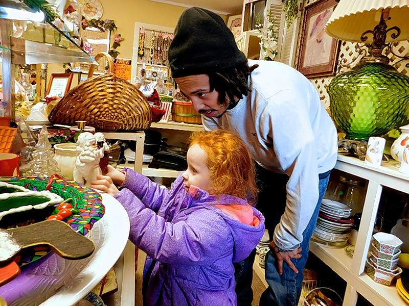 "Victoria Keeling, 4. and her stepfather, Dimitri Johnson, of Johnston City, look at some of the items at the thrift store. ""Everything in here is affordable,"" he said. ""It's a good place to be."""