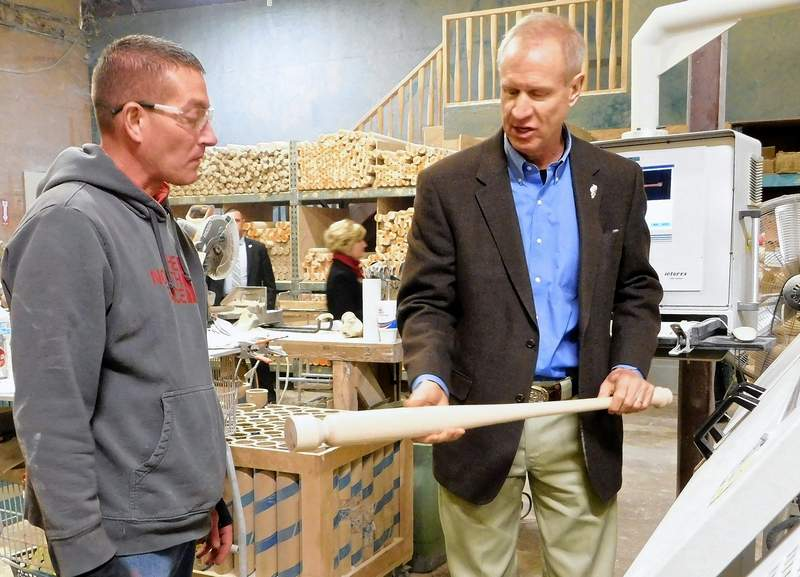 "Illinois Governor Bruce Rauner inspects a bat created by lathe operator Matt Hopson (left) during a visit to Dinger Bats in Ridgway on Thursday.  Rauner tool the unfinished bat with him.  ""I'm just going to set this in my office,"" he said."