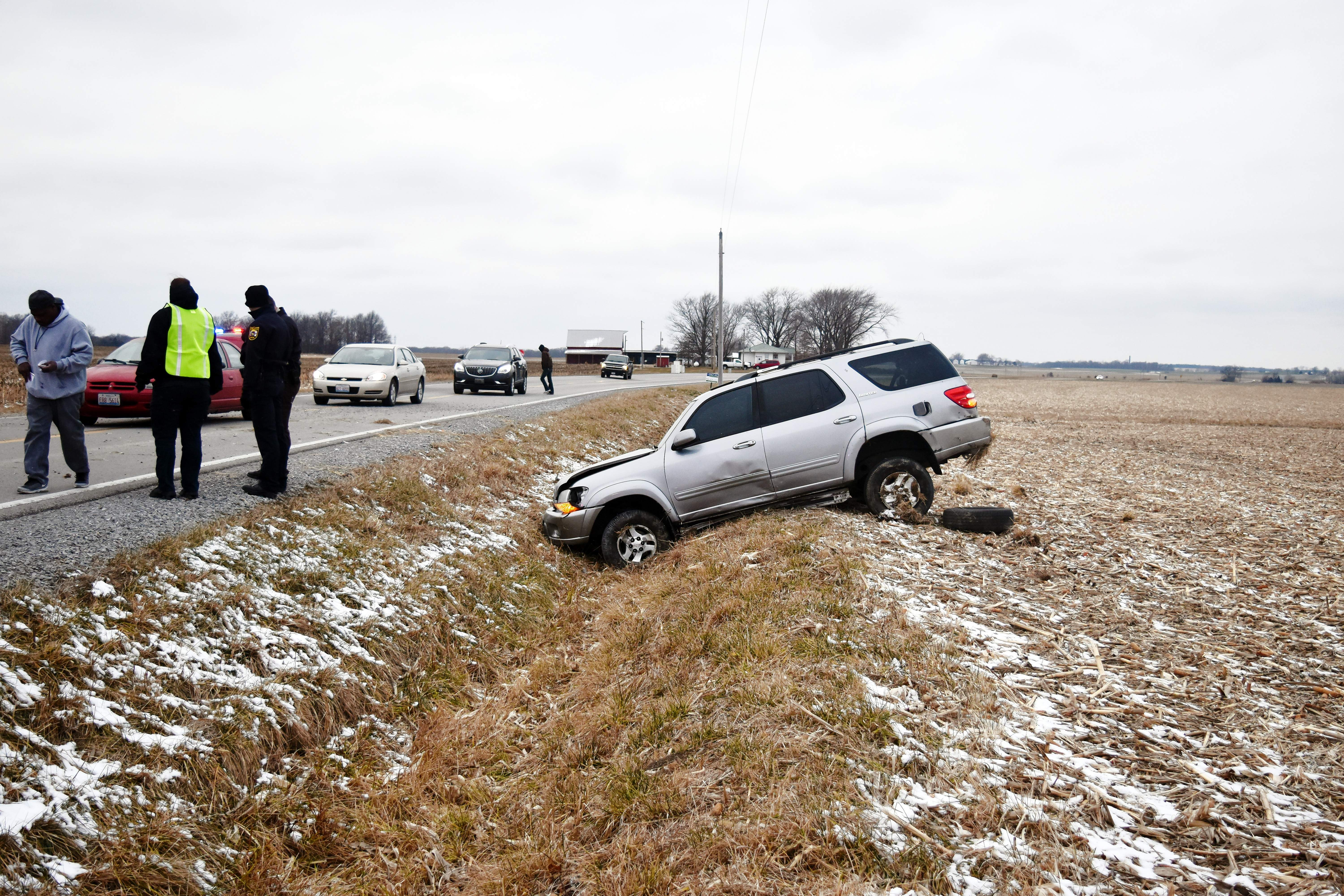 Emergency services personnel tend to a single-vehicle rollover accident on Wine Hill Road west of Shiloh Hill Road on Tuesday. The driver escaped the wreck with only minor injuries.