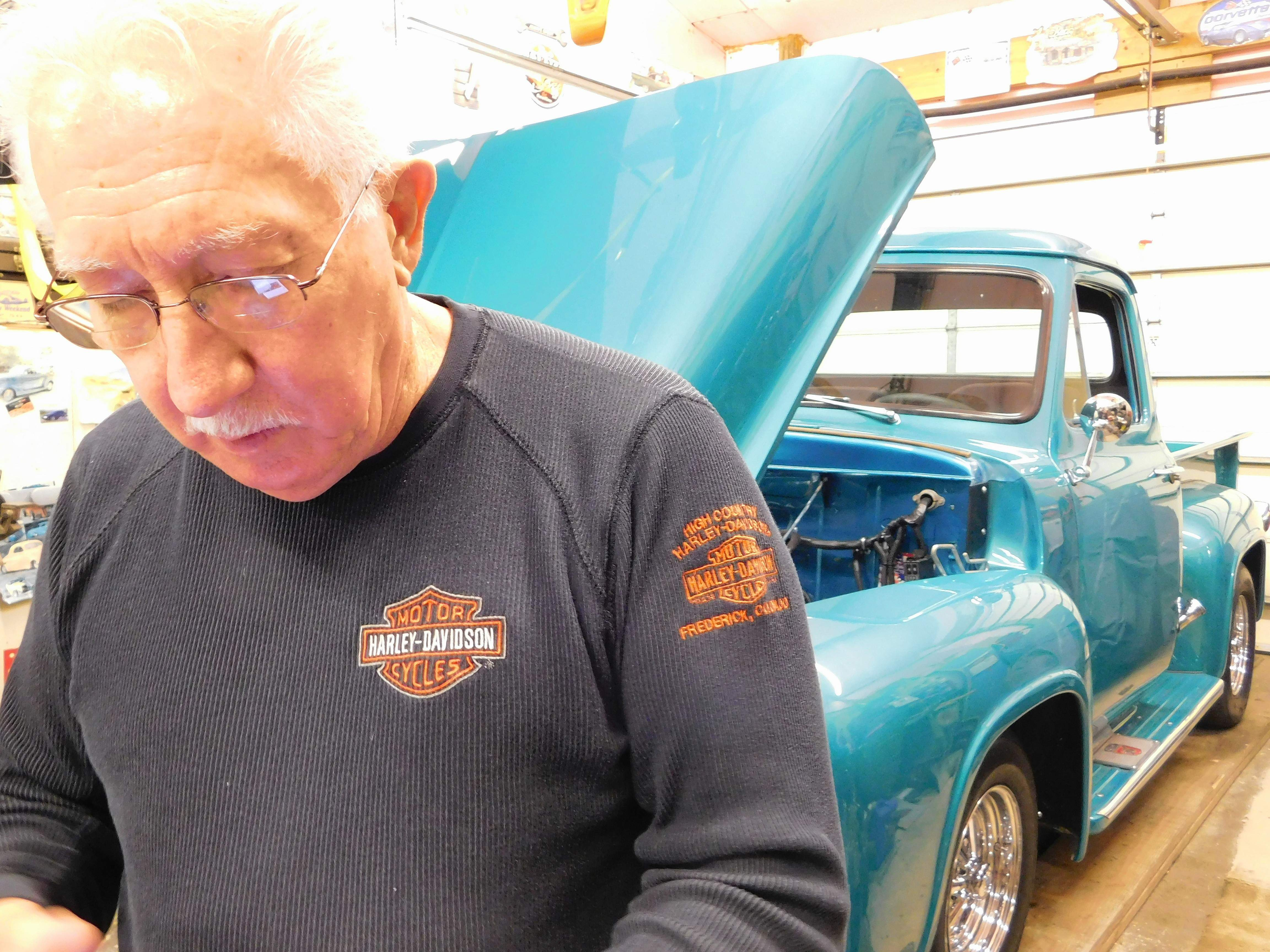 Bob Gentry searches for a photo of one of the vehicles he has restored.  The 71-year-old retired coal miner credits his friend, Jerry Kee, for sending him to Dr. Mwansa at Marion's Heartland Regional Medical Center who diagnosed his need for bypass surgery.