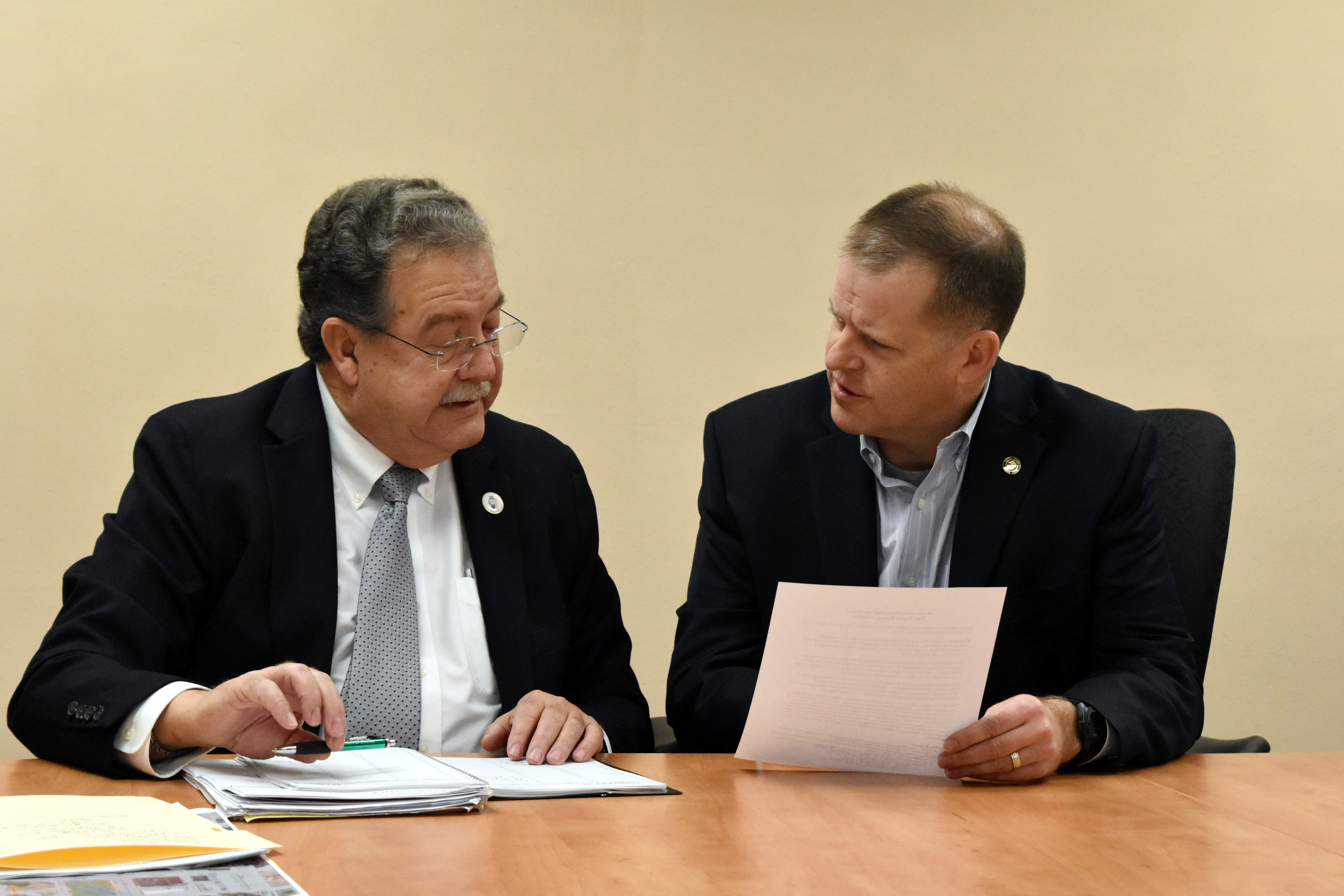 Four County Highway Coalition Chairman Marc Kiehna (left) speaks with State Sen. Paul Schimpf (R-Waterloo) prior to Tuesday's meeting. The pair are looking at an informational sheet about the highway proposal.