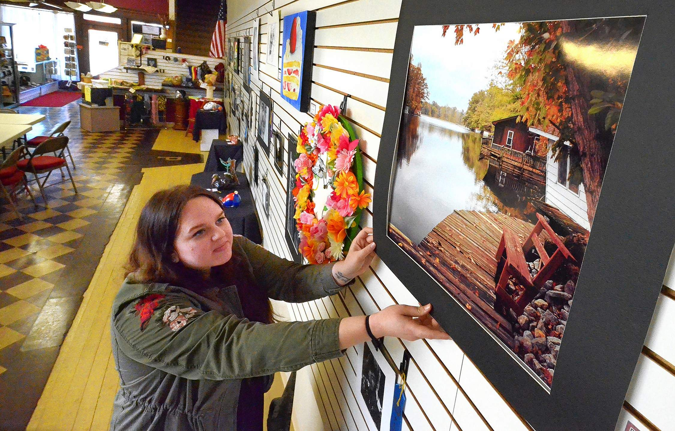 Here, LEAA volunteer Emily Key of Marion levels a photograph in the show taken by Marion High School student Jordan Bloodworth titled, 'A Seat At Water's Edge.'