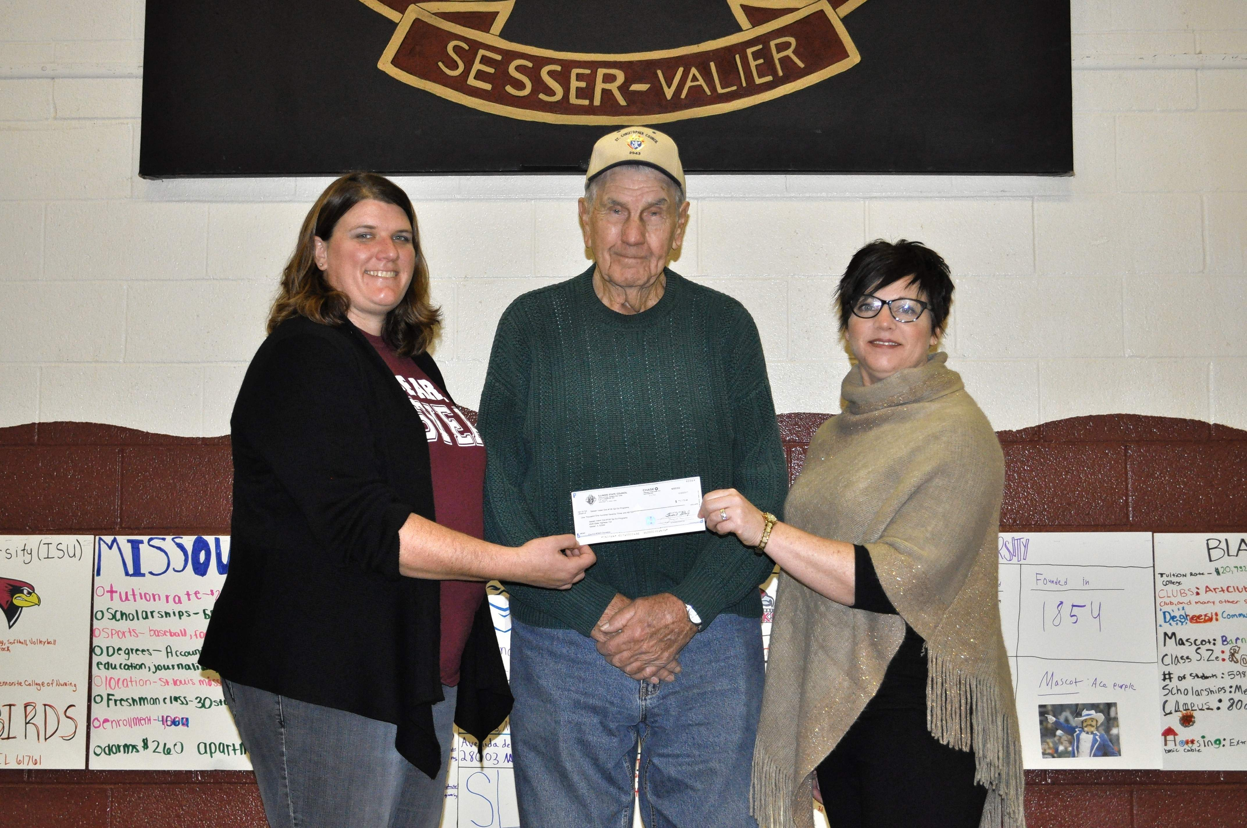 Junior high special education teacher Rachel Payne (left) and Sesser-Valier High School principal Natalie Page receive their Tootsie Roll check from Christopher KC member James 'Tooter' Lovelady of Sesser.