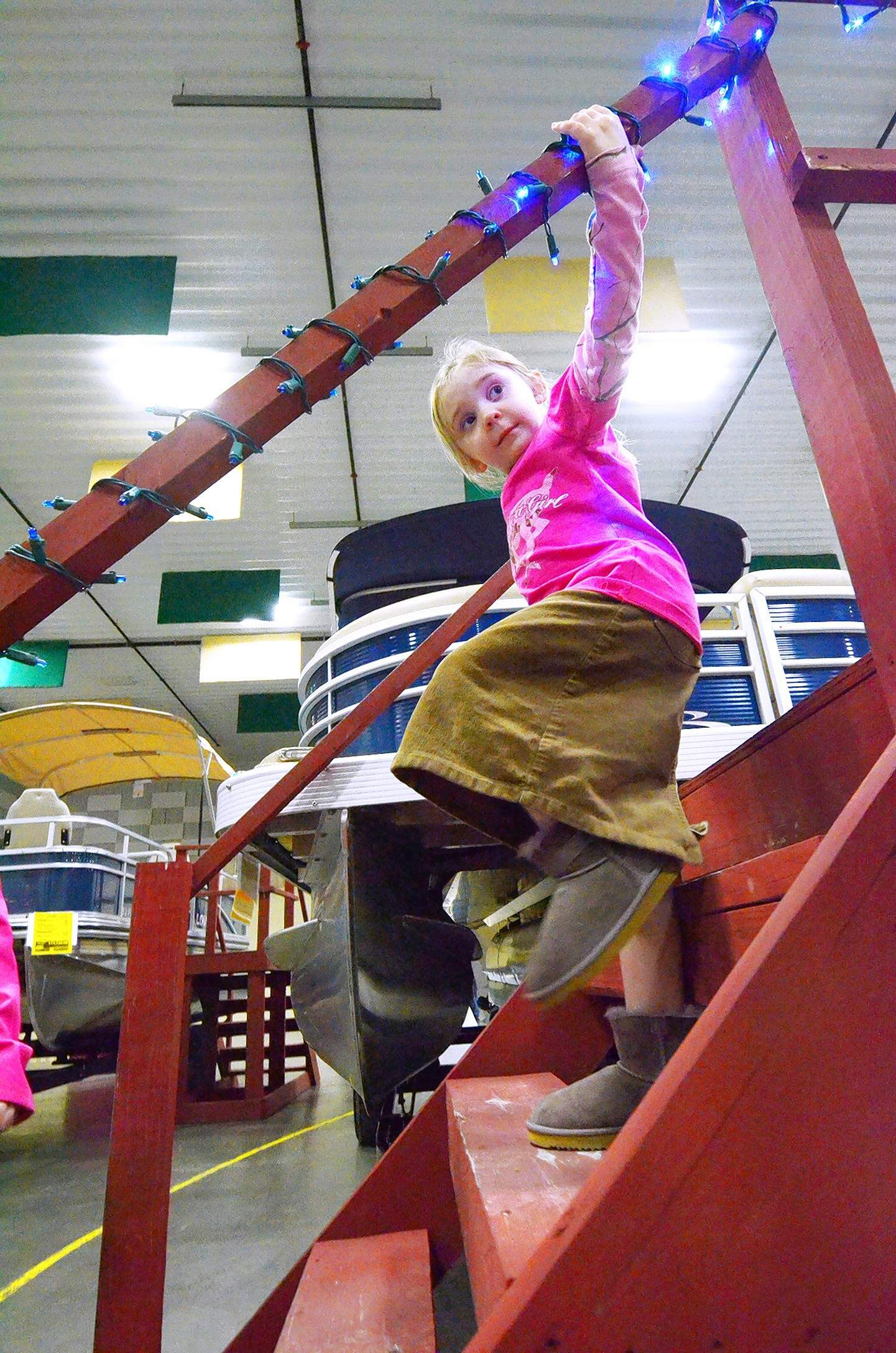 Four-year-old Sarah Lessar carefully makes her way down the steps leading to a new pontoon boat that she and her mother had just checked out at the show.