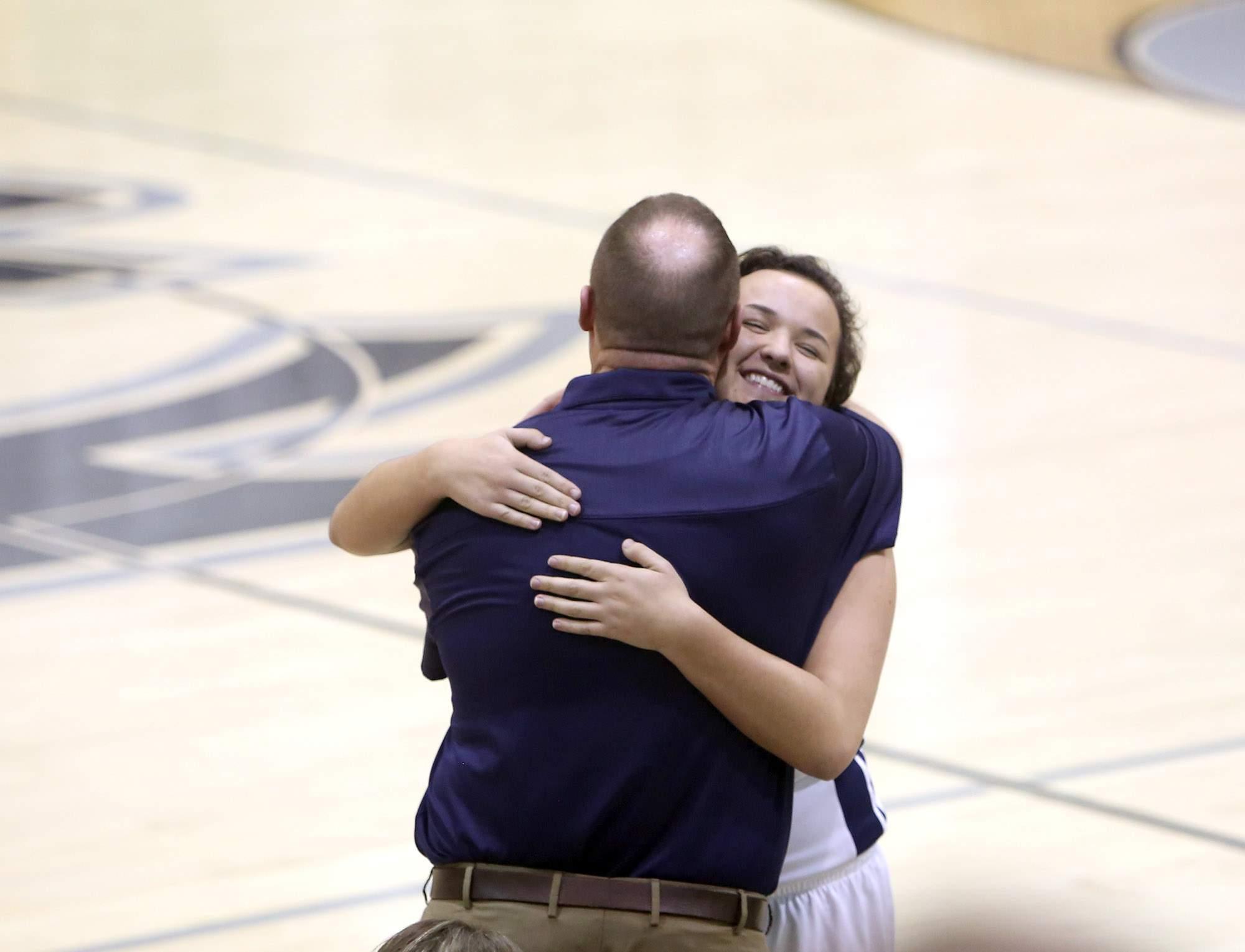 Matt Crain embraces senior Sydney Monje in the final minute.