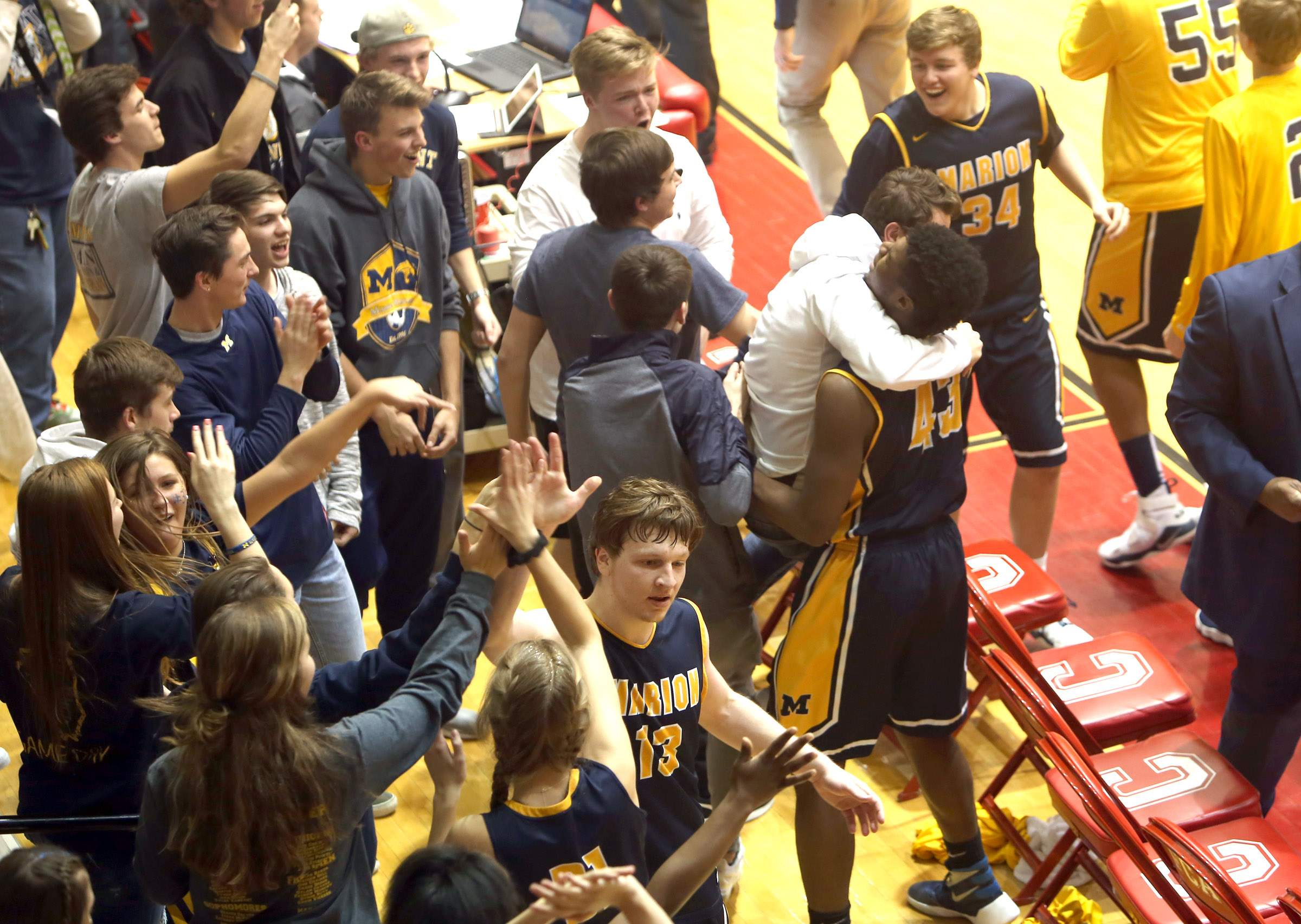 """Marion seniors Justin Saddoris and Terrell Henderson make a quick visit to the """"maniacs"""" after Tuesday's victory."""