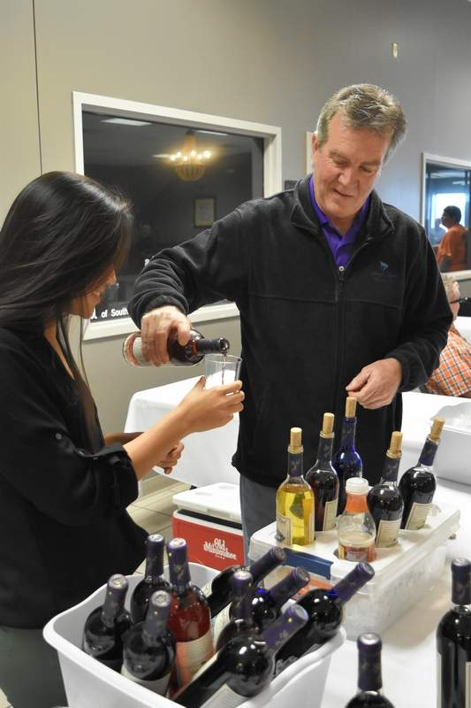 Allen Dossey, right, owner of Purple Toad Winery, pours a glass of wine for Koerner Distributor Inc. rep Shannon Effron at the Taste of Southern Illinois Sunday in Harrisburg.