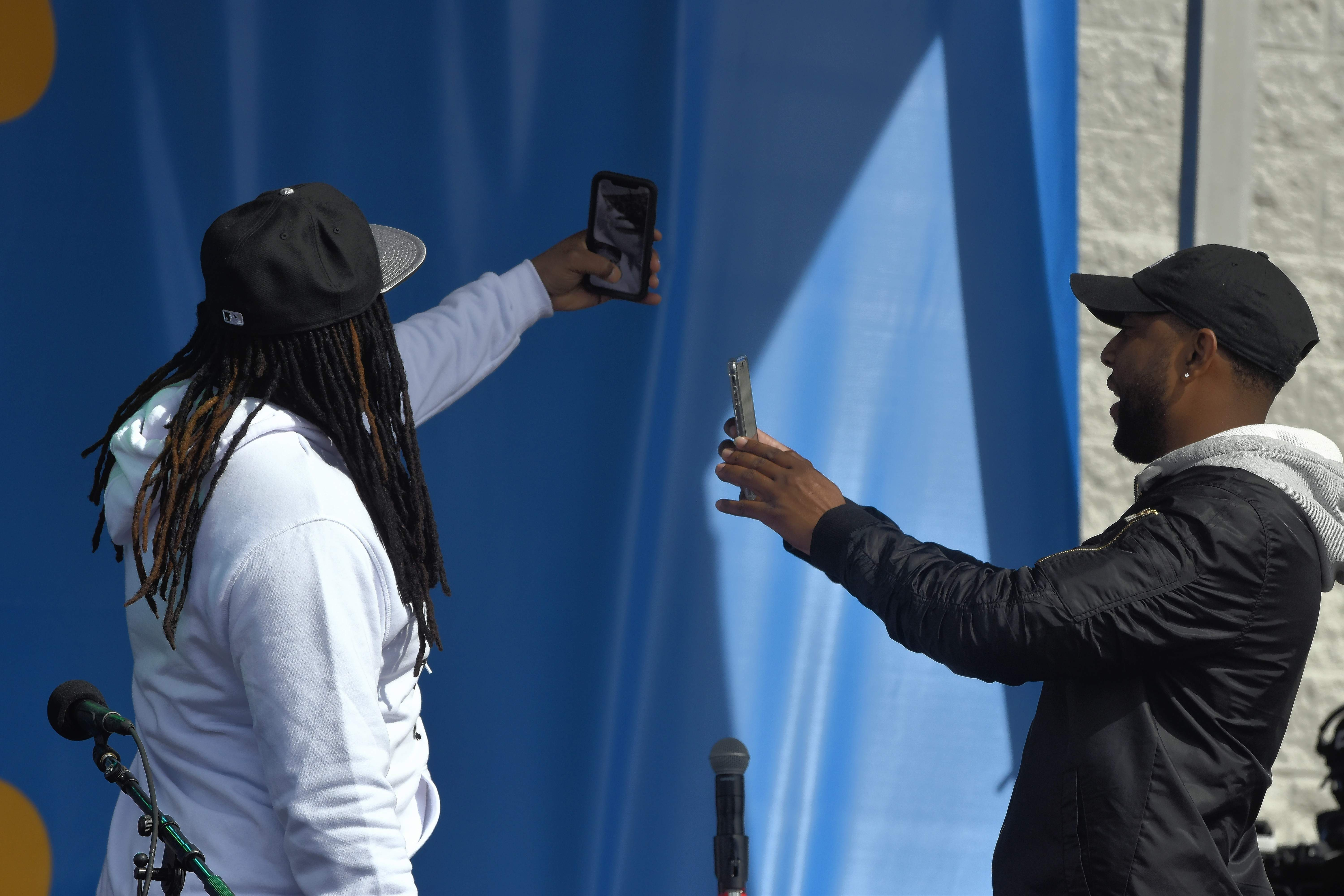 Remix artist D.J. Suede and a crewmember take selfies with the crowd in the background prior to the Mason Ramsey concert Wednesday.
