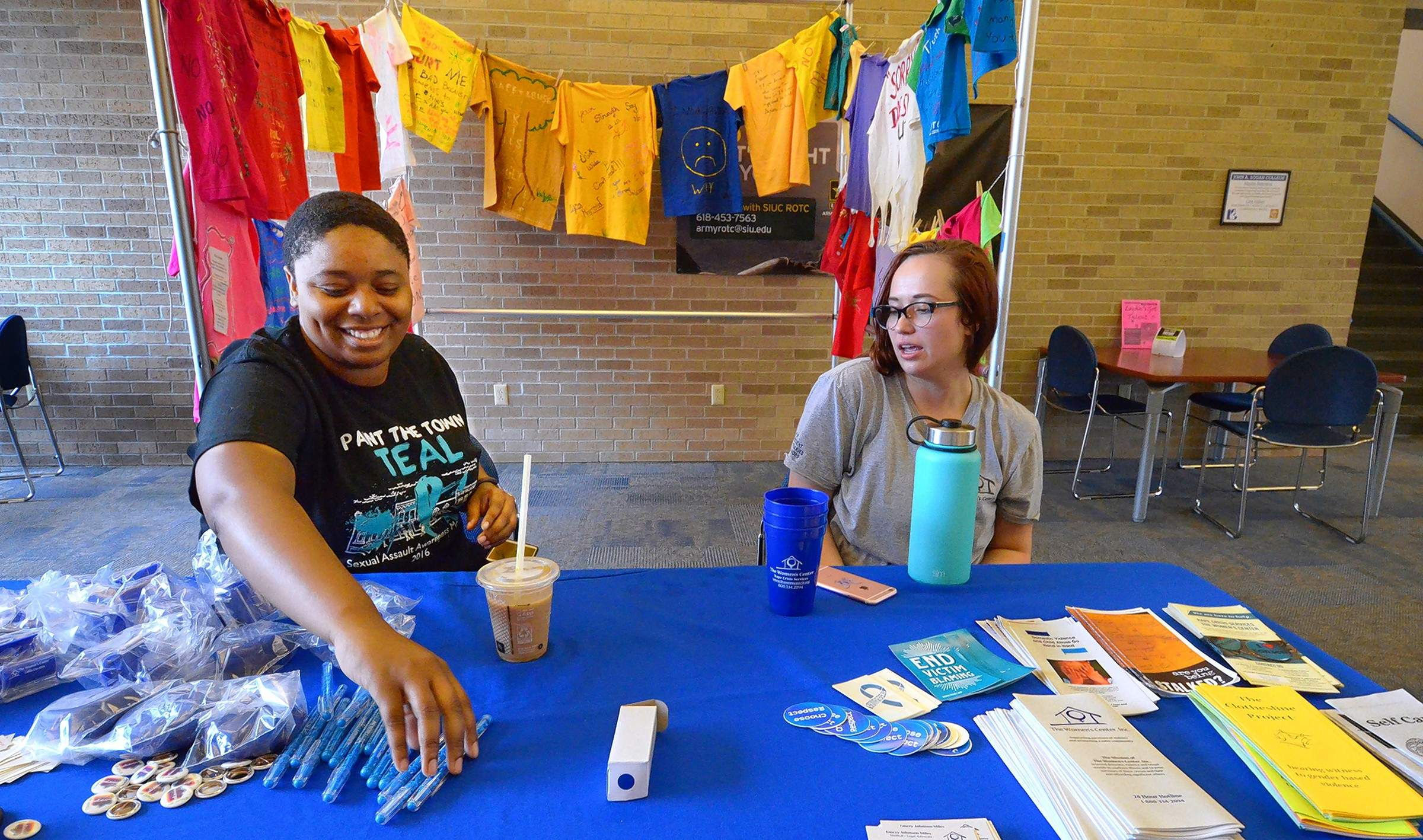 Desiree Brown and Allyson Stevens spent several hours Tuesday at this sobering display of T-shirts, which feature decorative expressions of feelings by victims of violence and abuse.