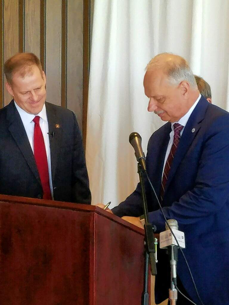 SIU Chancellor Carlo Montemagno, right, signs a memorandum of understanding to study two Southern Illinois recreational sites for ways to encourage economic growth, as state Sen. Paul Schimpf looks on.