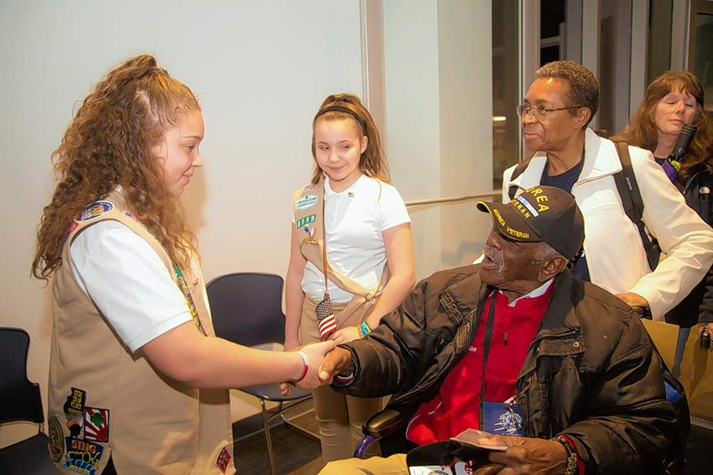 Girl Scout Paris Baskerville shakes hands with Korea veteran Orlen Sims of Carbondale before escorting him through the hundreds of people gathered at Veterans Airport in Marion Tuesday night to welcome him and other veterans home from this week's Honor Flight. Sims, along with more than 30 other veterans, had the opportunity to fly to and from Washington, D.C., to visit the various veterans memorials.