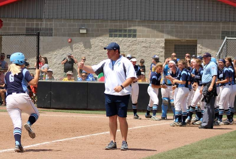 Panthers coach Alan Engelhardt fist bumps Megan Mayo on her game-tying homer as teammates gather at the plate.