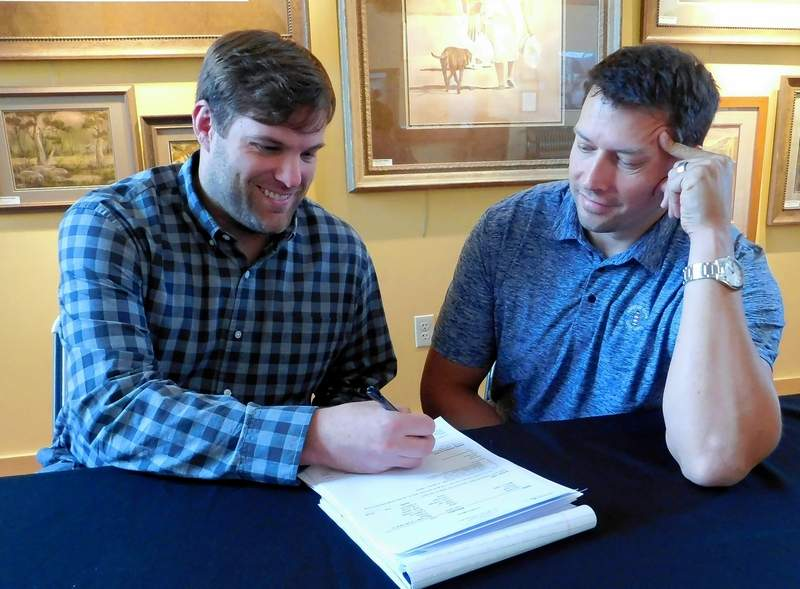 Josh Benson, executive director of the Marion Cultural and Civic Center, watches Cody Dunbar of M5E sign the contract.