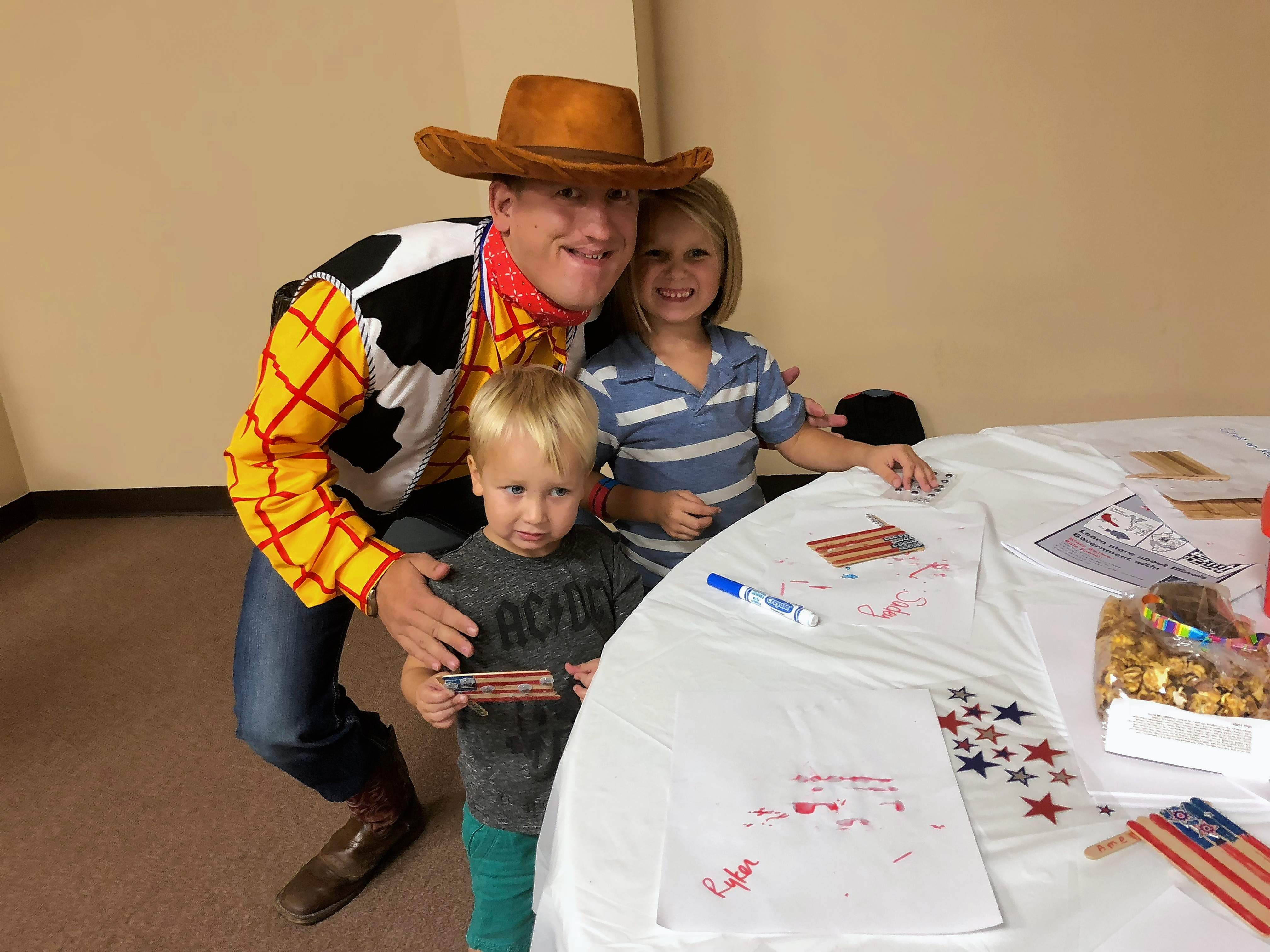 "Ryker Fricke, left, and his sister, Sadey, pose with ""Woody"" while doing crafts in the children's area at the Southern Illinois Made Expo at the Marion Pavilion on Sunday. Ben Fritts of Harrisburg said he enjoys playing the Toy Story character because ""it's so much fun for the kids."""