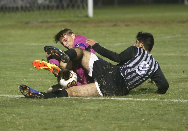 Marion goal keeper Camden Dodds collides with Carbondale's Sajad Nassar in the second half of Tuesday's match.