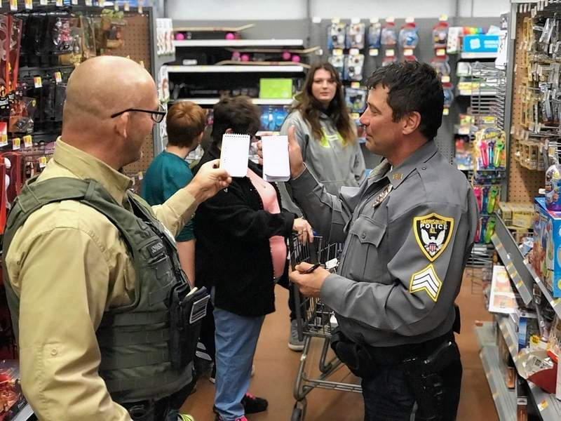 "Saline County Sheriff James ""Whipper"" Johnson, left, and Harrisburg Police Department Sgt. Curt Hustedde compare shopping lists as they assist with Saline County's Shop with a Cop program Saturday at the Harrisburg Walmart."