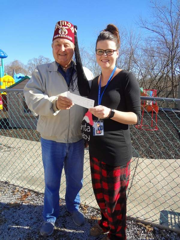 Roland Wagner, left, Randolph County Shrine Club member and Ambassador of the Ainad Shrine, presents a $100 check to Mariah Adams of Western Egyptian Head Start, in Chester.