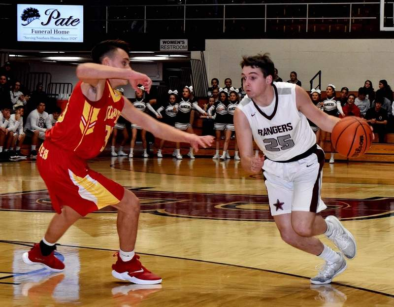 Senior guard Mason Wills drives toward the bucket around Murphysboro's Corbin Guthman during a prep game at Rich Herrin Gym on Friday. Wills scored five points in the two-point loss to the Red Devils.