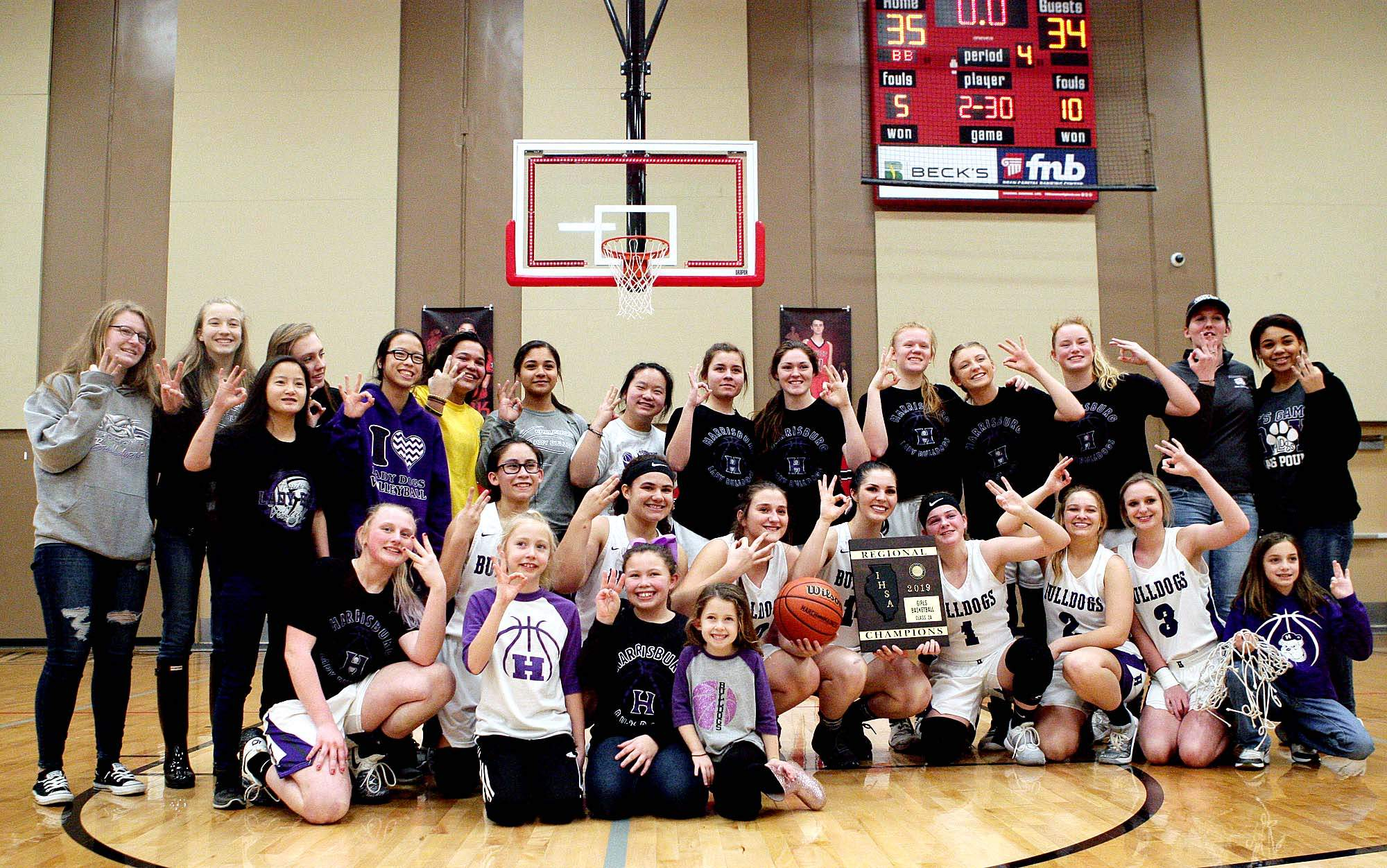 Members of the Harrisburg High School girls' basketball team pose with the IHSA Class 2A Regional Championship after knocking off Anna-Jonesboro 35-34 Thursday night at the Wayne City Regional. It was the third straight regional title for the Bulldogs.
