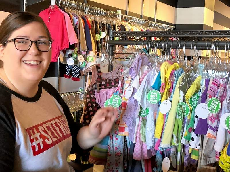Molly Stearns of Two Bugs and a Bean Children's Resale Boutique in Carbondale readies items for sale.
