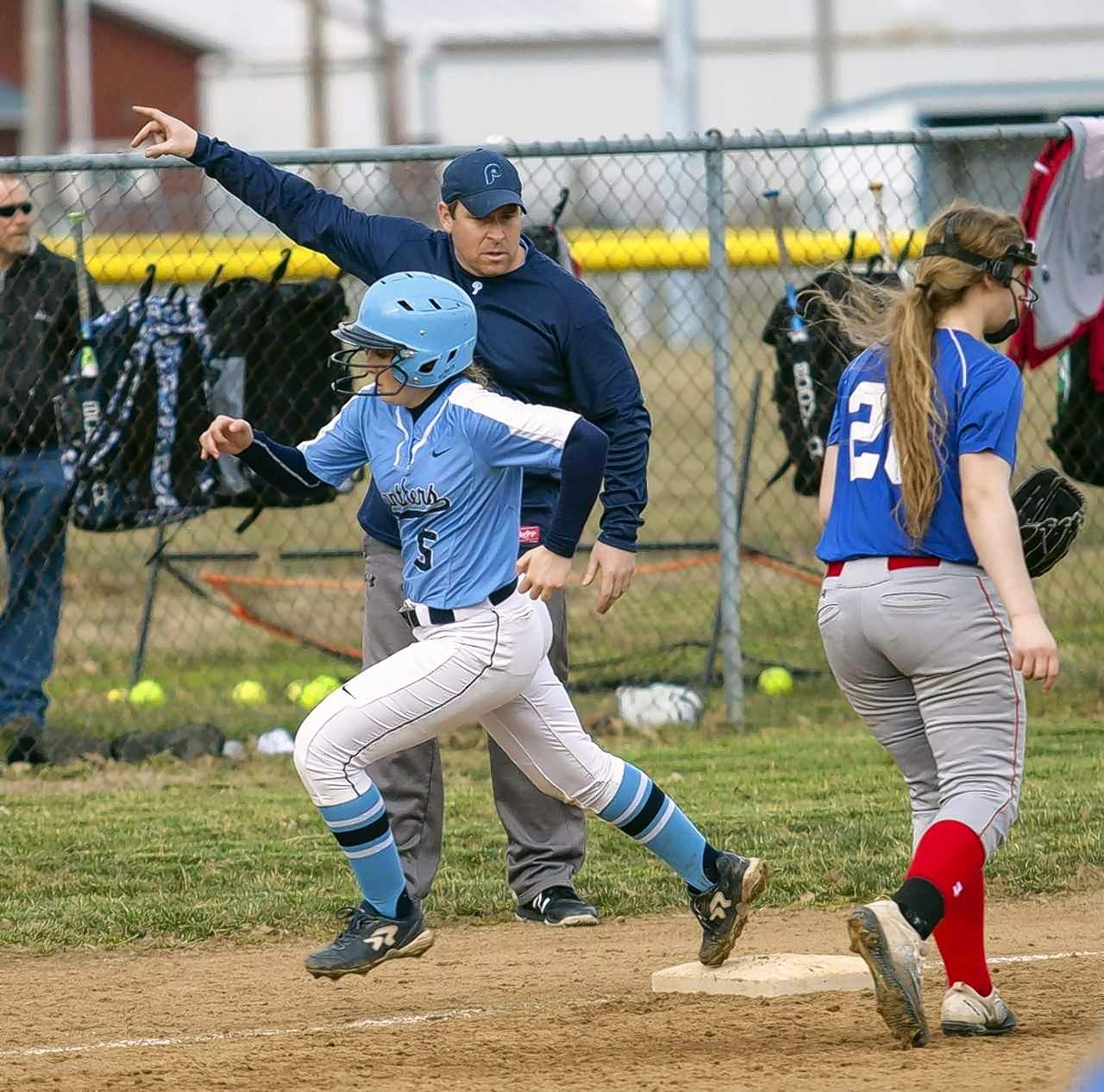 PCHS softball coach Alan Engelhardt sends runner Lynlee Lindner home for a run.