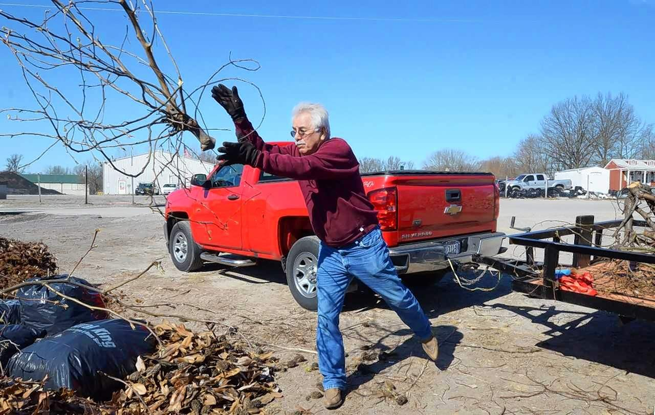 Paul Reed of Marion tosses limbs onto the pile at the Marion yard waste dump this week, joining others who take advantage of the free service to residents by the City of Marion.