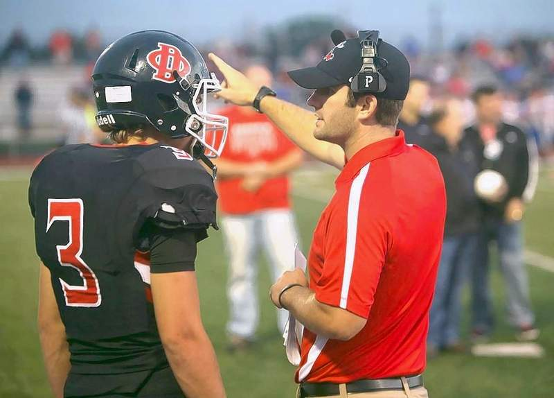 Indians head coach AJ Hill gives instructions to his quarterback during a game last fall.