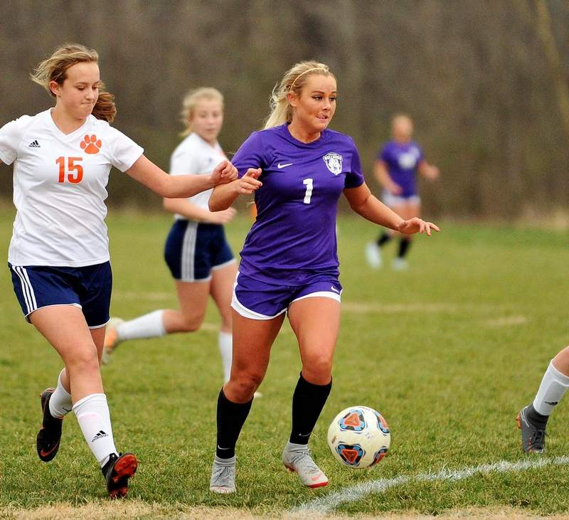 Devin Butler moves the ball past Carterville defenders on her way to scoring a goal in the second half of play.