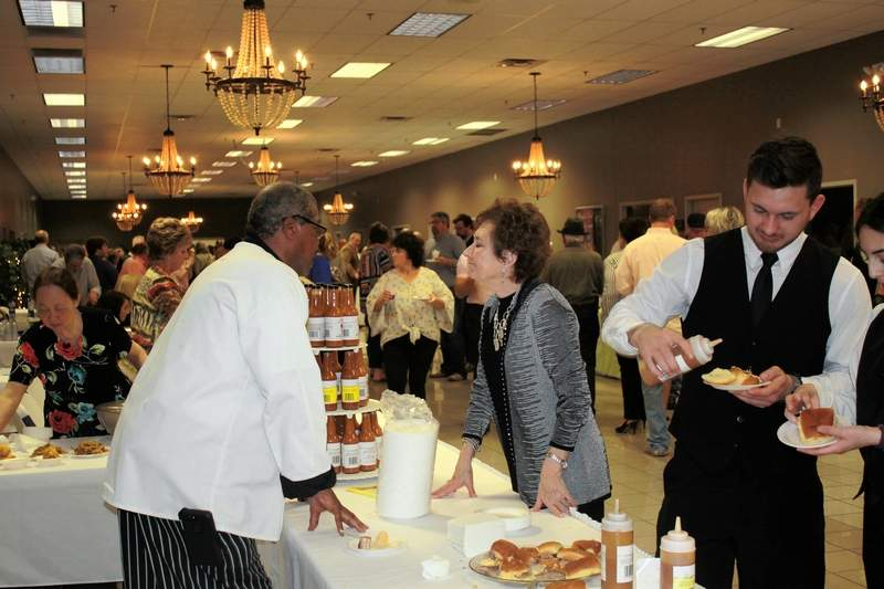 Rupert Johnson, left, owner of Johnson's Southern-Style Barbecue, speaks to an attendee of the Taste of SI Sunday. Johnson's Barbecue has been a staple of Taste of SI for the past 20 years.
