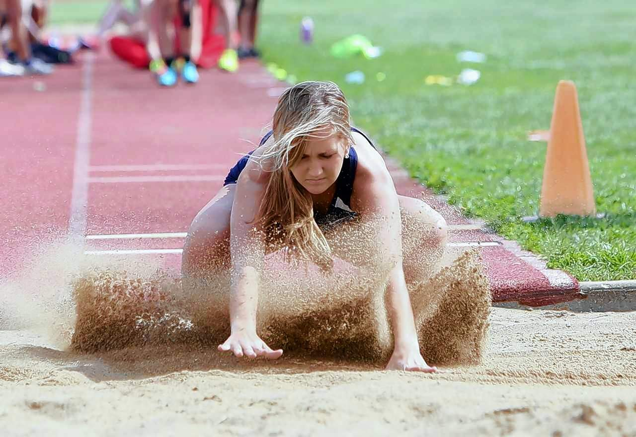 Molly Pugh of the Wildcats hits the sand in the long jump event.
