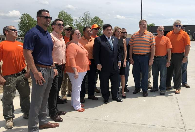 Gov. J.B. Pritzker poses with local workers and officials, part of the team responsible for the construction of the Halfway Road expansion in Marion.