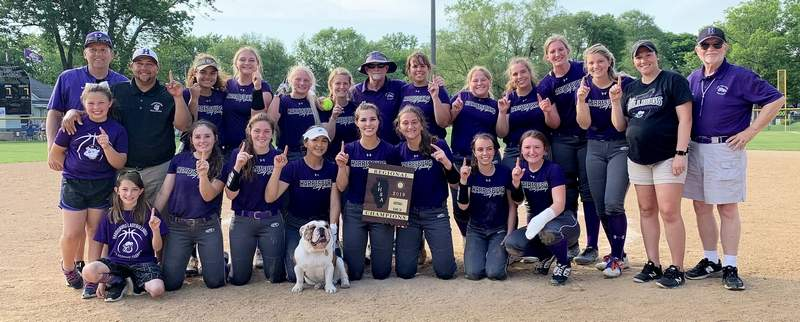 Members of the Harrisburg coaching staff, along with the Harrisburg softball team, pose with the championship plaque after defeating Eldorado 8-7 Friday to claim the school's first regional title since 2014.