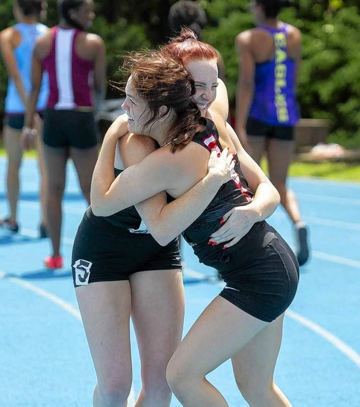 Madison Davis and Bailey Harsy embrace following the team's win in the 4x100 meter relay.