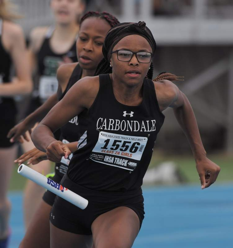 The baton falls on the exchange between Carbondale's Serenity Riley, front, and Kiara Cobb in the 800-meter relay during the Class 2A girls state track and field preliminaries in Charleston May 17.